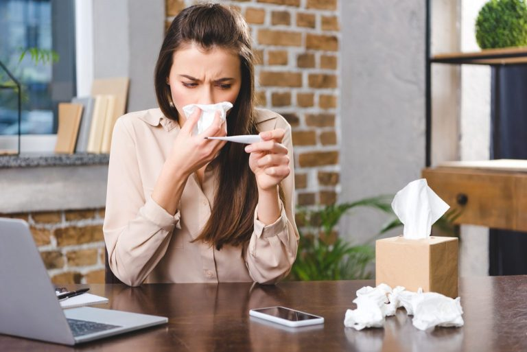 Girl blowing her nose into a tissue while reading her temperature