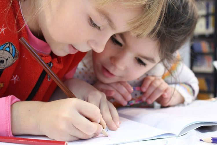 Two girls focused on writing in a notebook at school